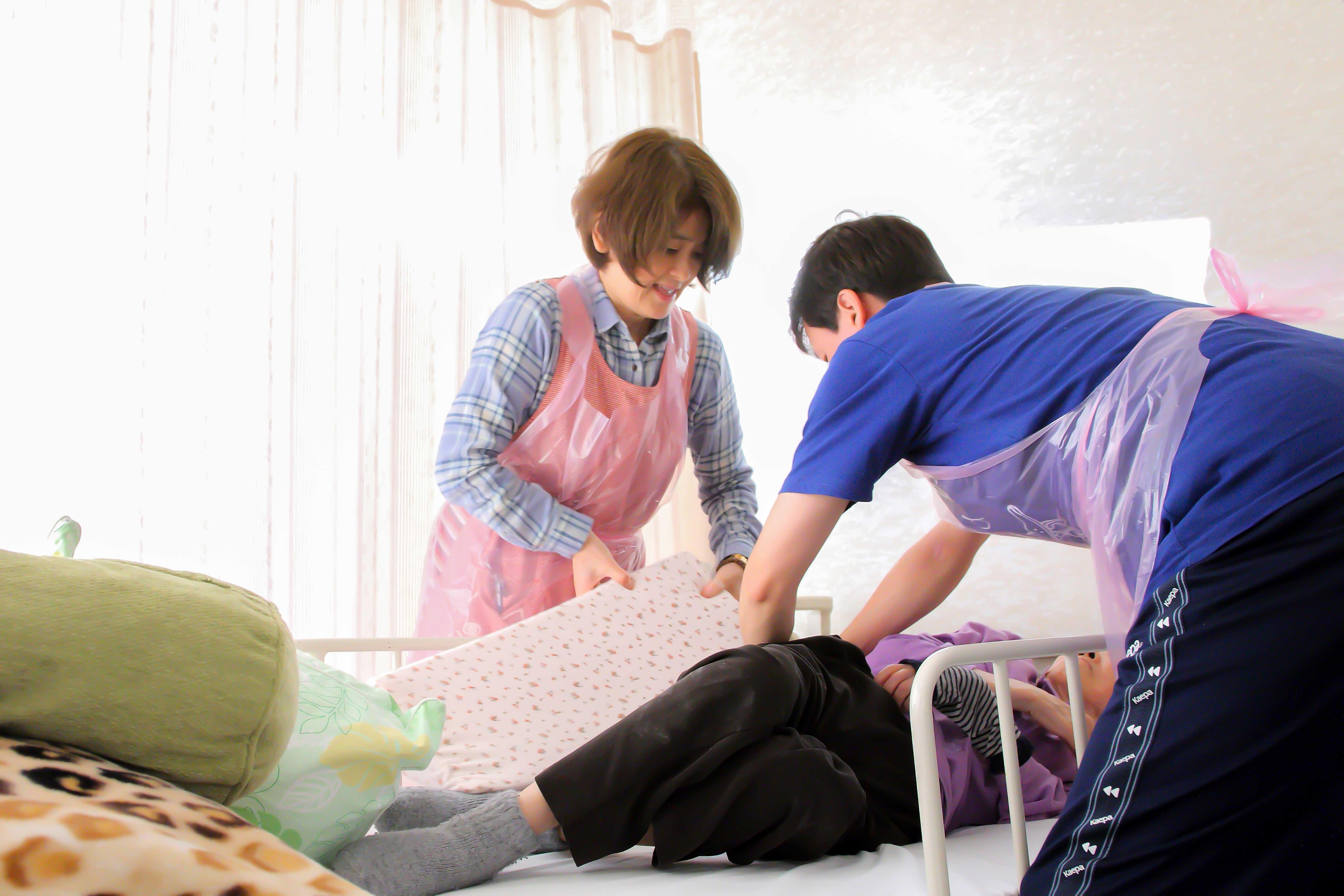 看護師と介護スタッフが一緒におむつ交換を行っている様子