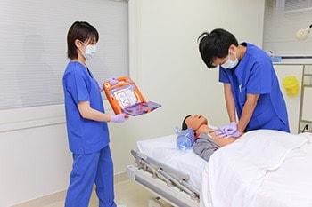 AEDのふたを開け準備している写真