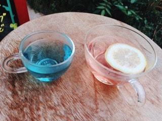 ウスベニアオイ(マロウブルー)のハーブティーにレモンを浮かべると綺麗なピンク色になっている写真
