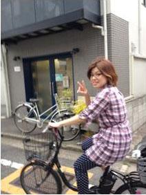 利用者さまのお宅へ訪問するため 自転車で移動する田川さんの写真