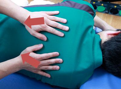 側臥位になり、第10肋骨より上部の胸郭を圧迫する、実践写真